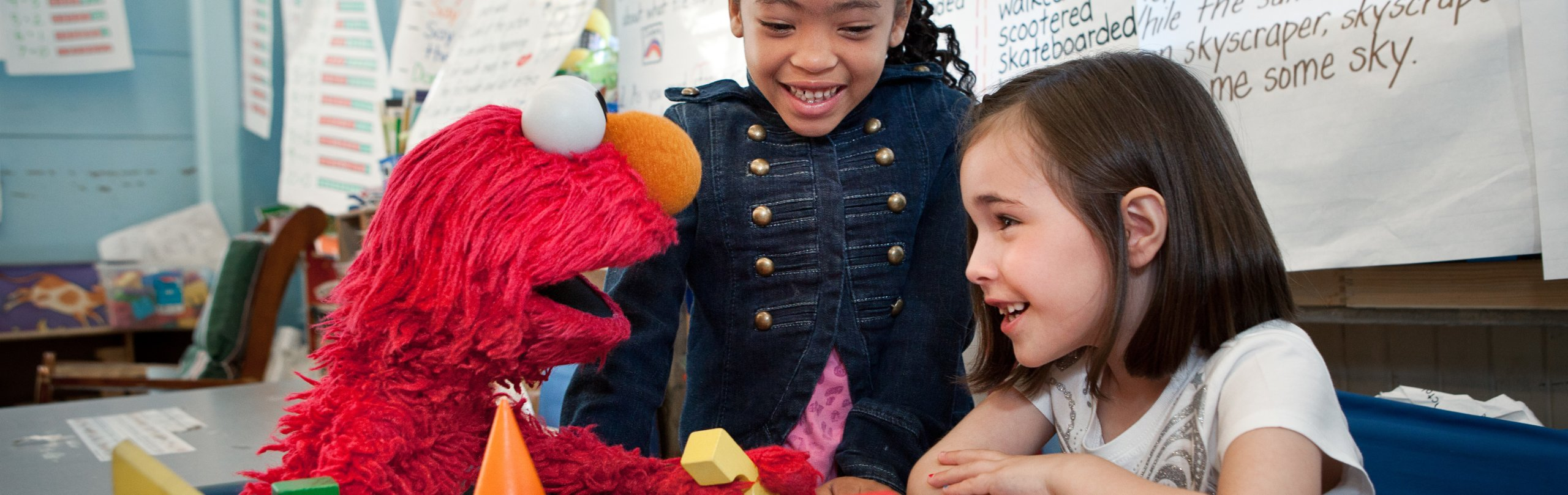 Elmo plays with blocks with two young girls