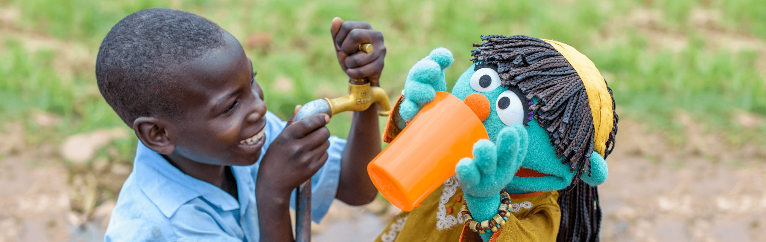 Young boy pours water for muppet Raya to drink from an orange cup
