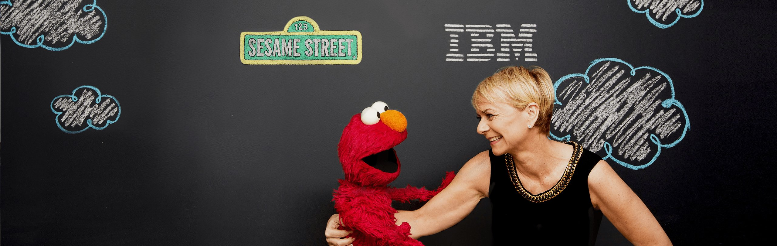 Elmo and woman smiling in front of Sesame Street and IBM logos