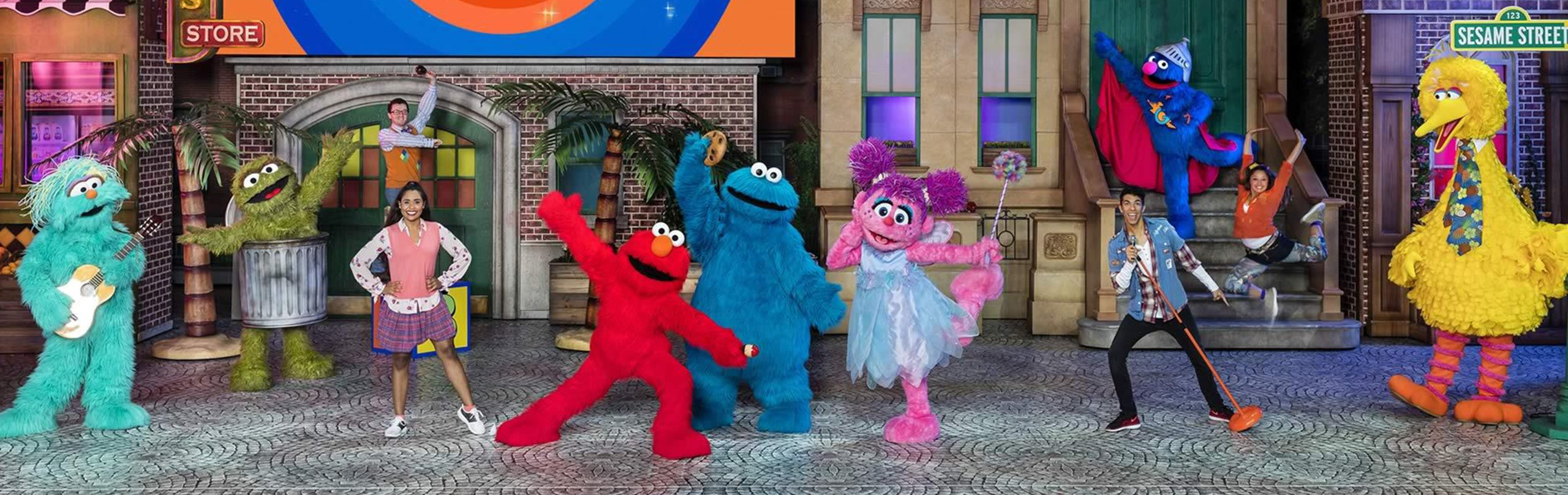 Sesame Street Muppets on stage dancing and posing with people