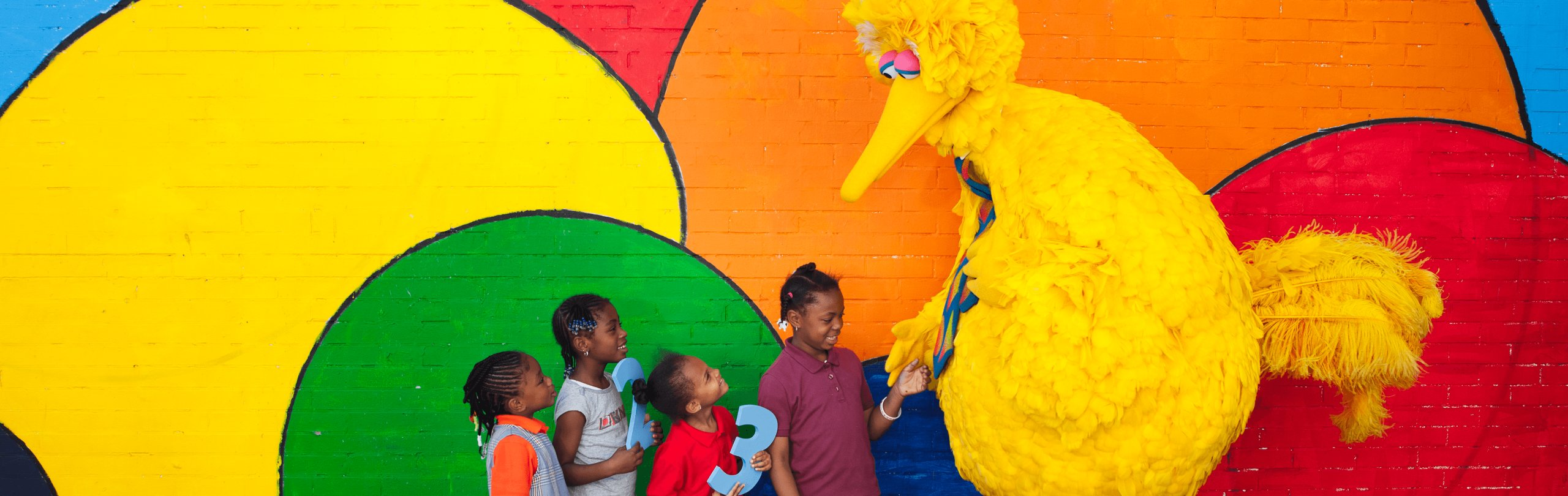 Big Bird with a group of children against a bright mural