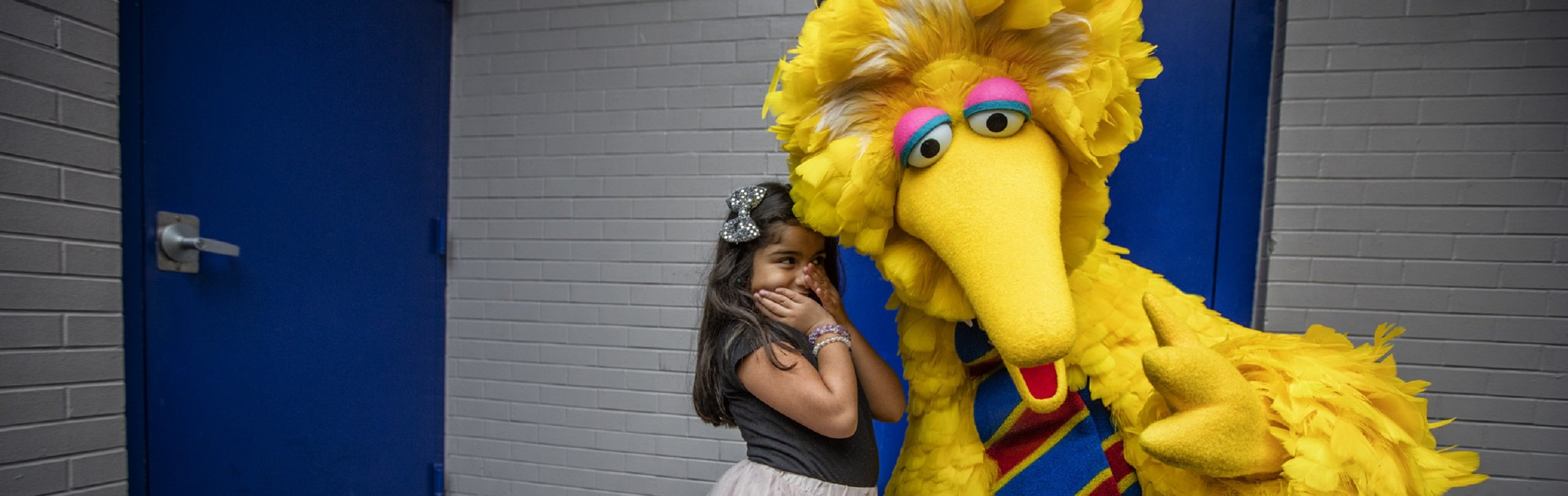 Little girl whispering to Big Bird