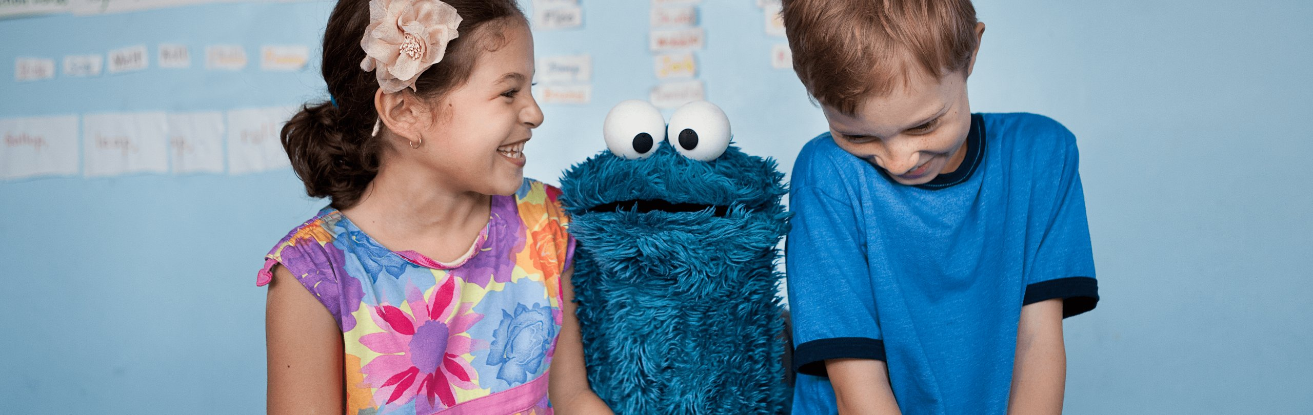 A girl and boy laugh while Cookie Monster looks between them