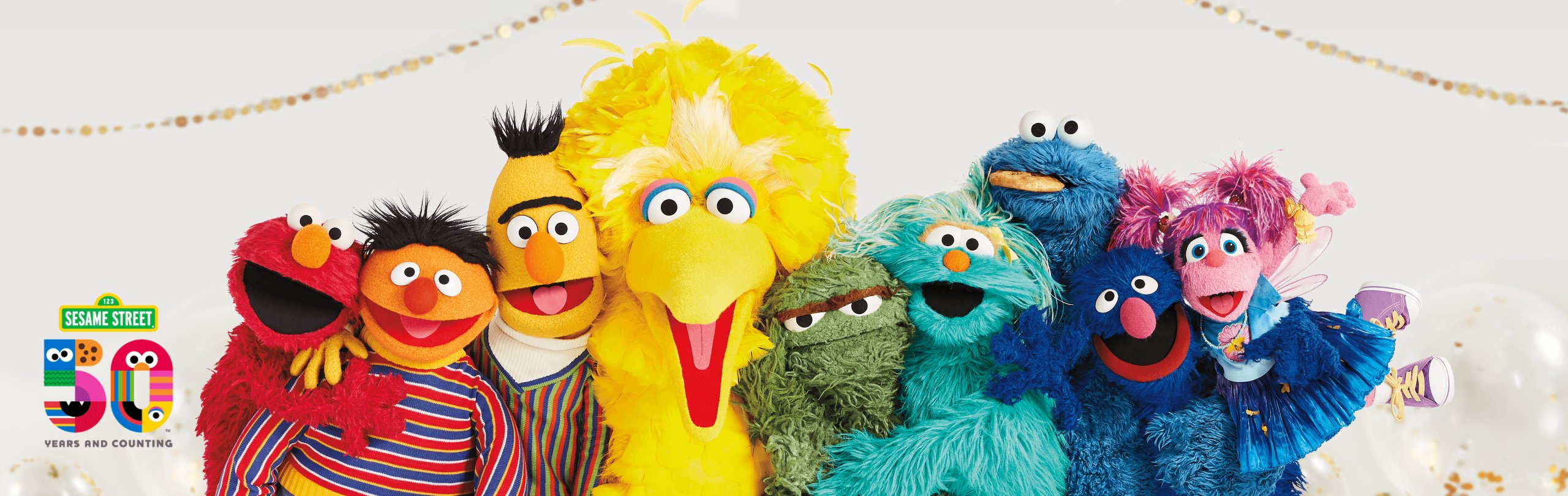 Group of Sesame Street muppets smiling and hugging