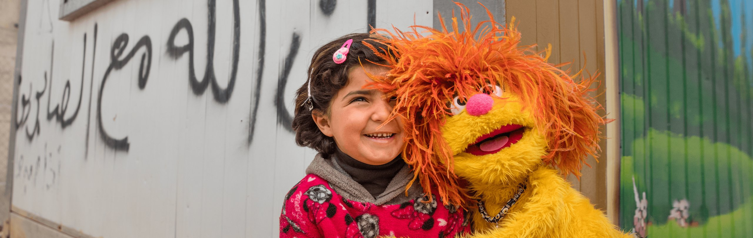 Muppet and Young Girl Smile and Hug