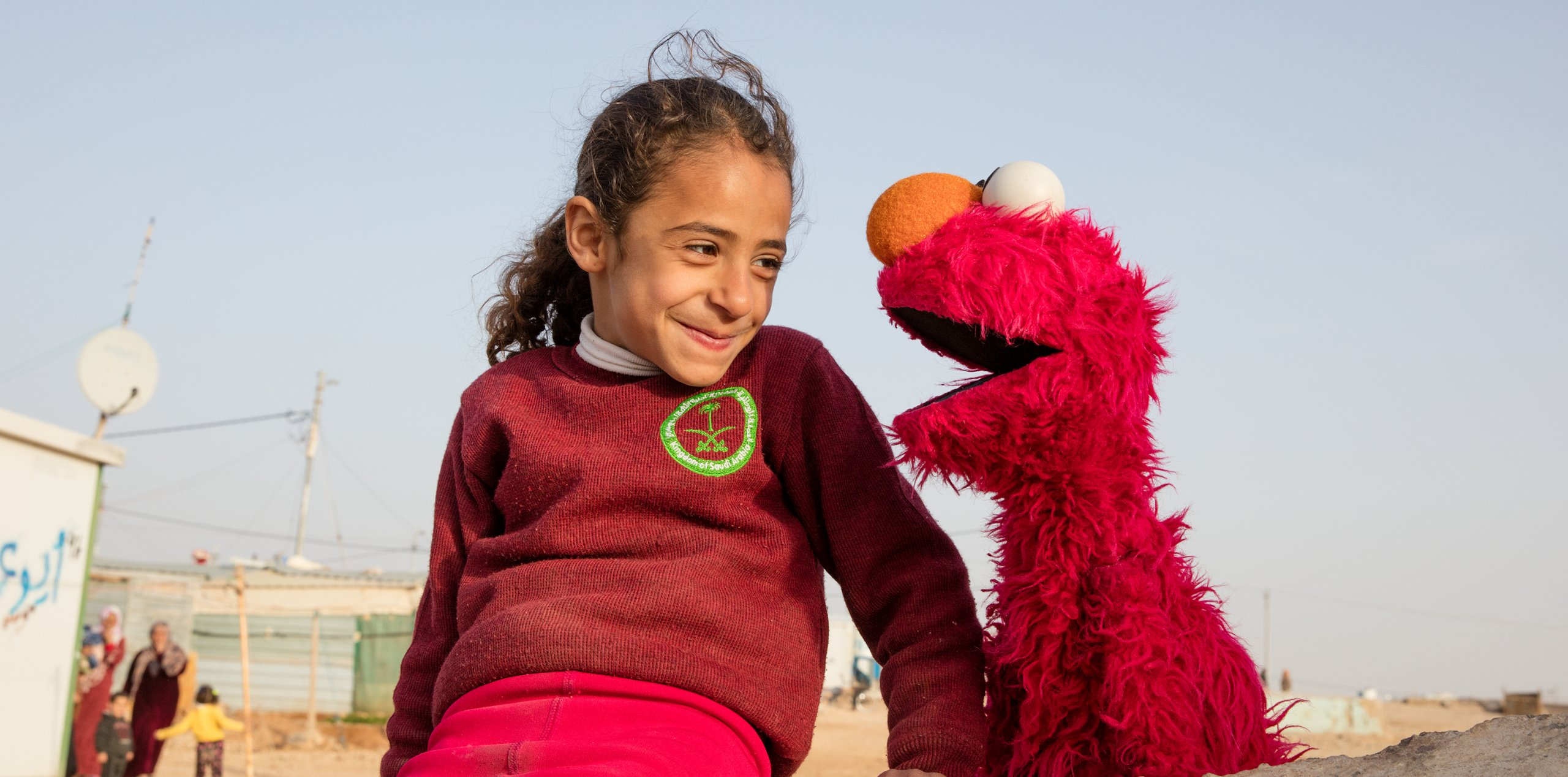A young girl smiles at Elmo as he talks to her