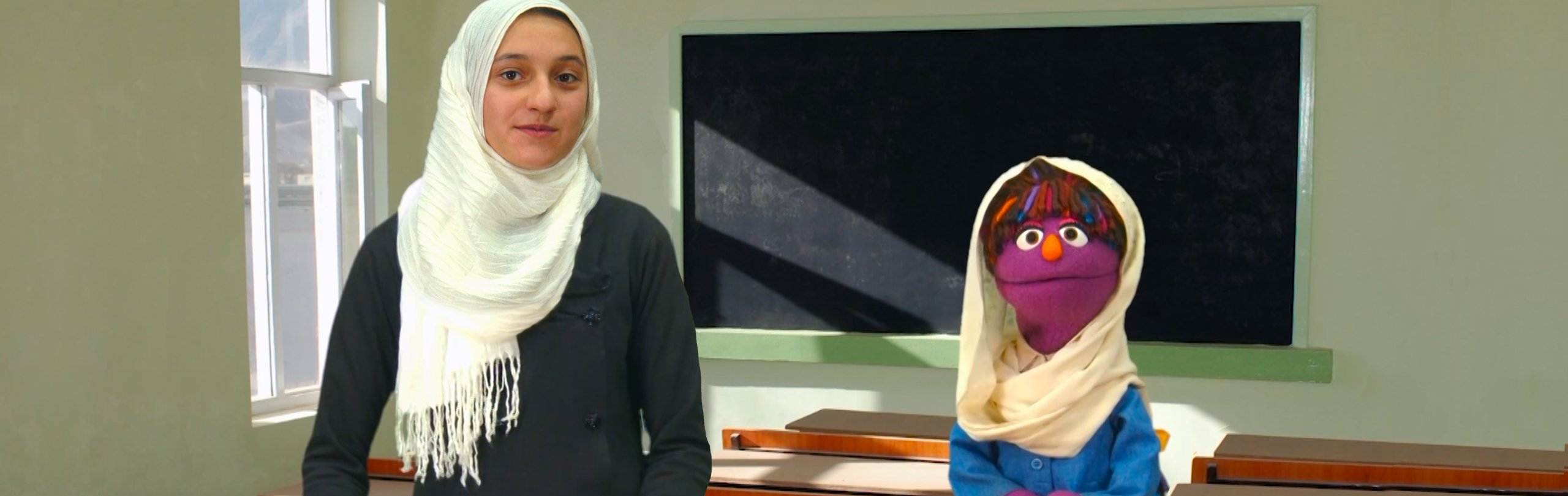A purple female muppet and a young girl stand in front of a blackboard looking at the camera
