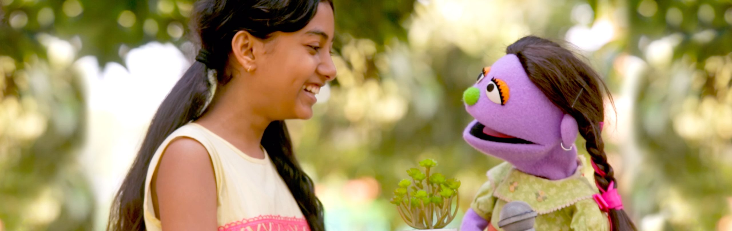 A muppet and a young girl smile and laugh together
