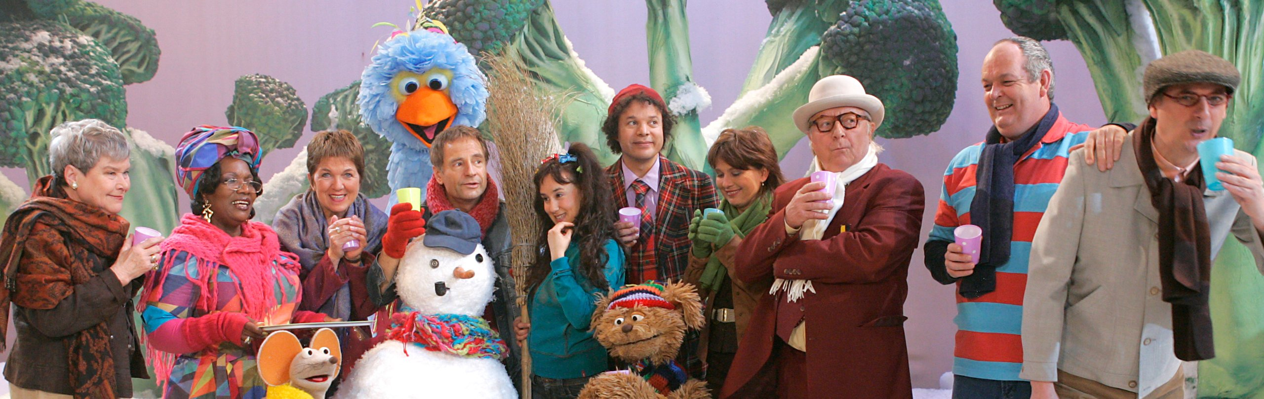 The cast of Sesamestraat poses with a snowman