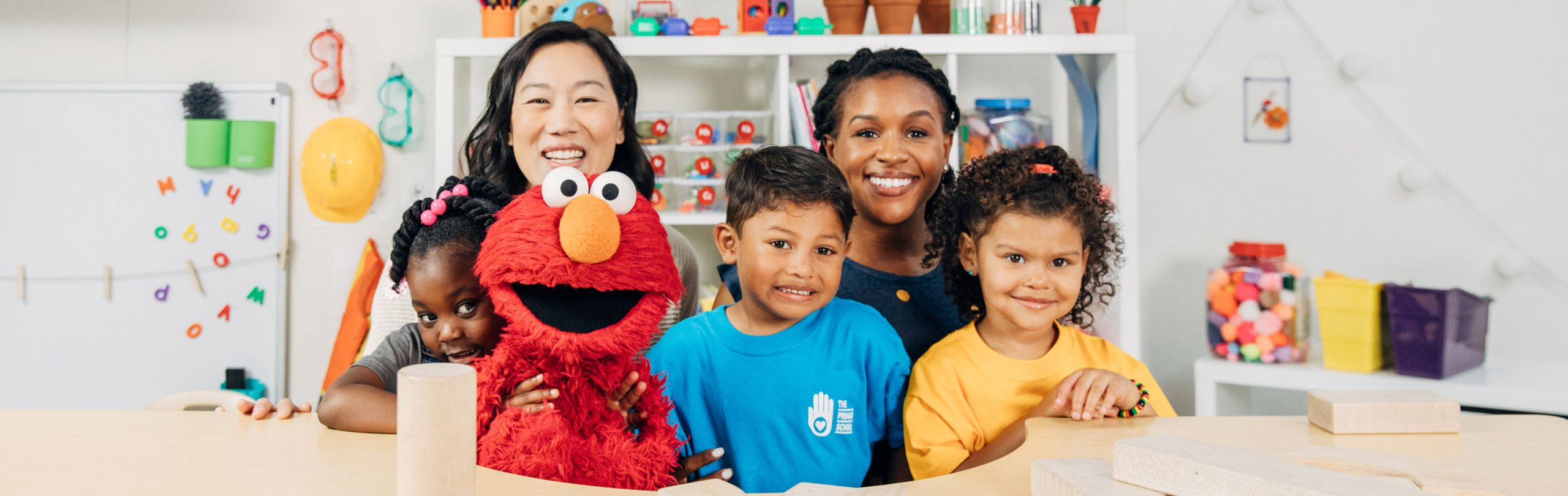 Elmo with teachers and children smile