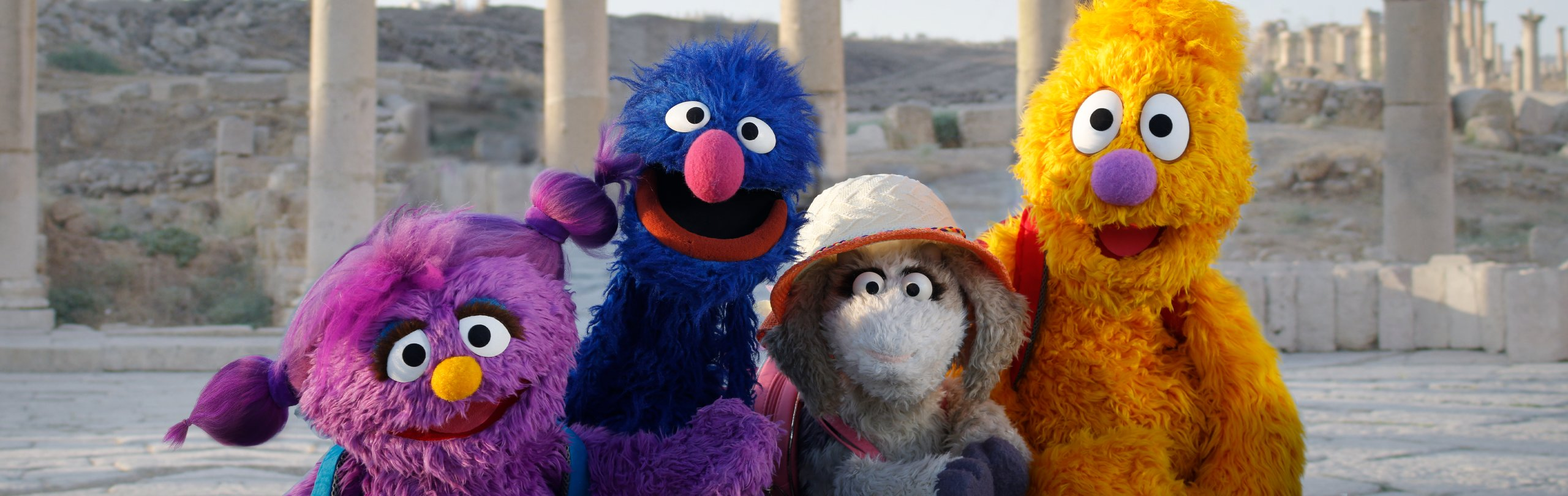 Basma, Grover, Ma'zooza, and Jad smile together outside