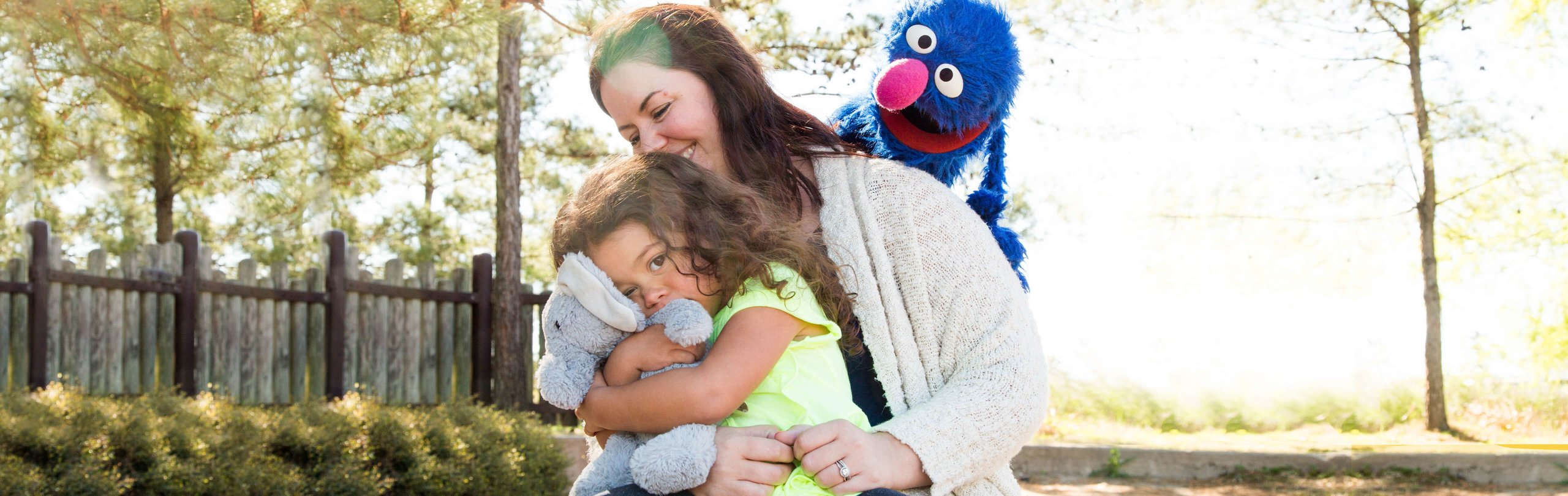 A child hugs a stuffed animal on a woman's lap while Grover smiles at them on a sunny day