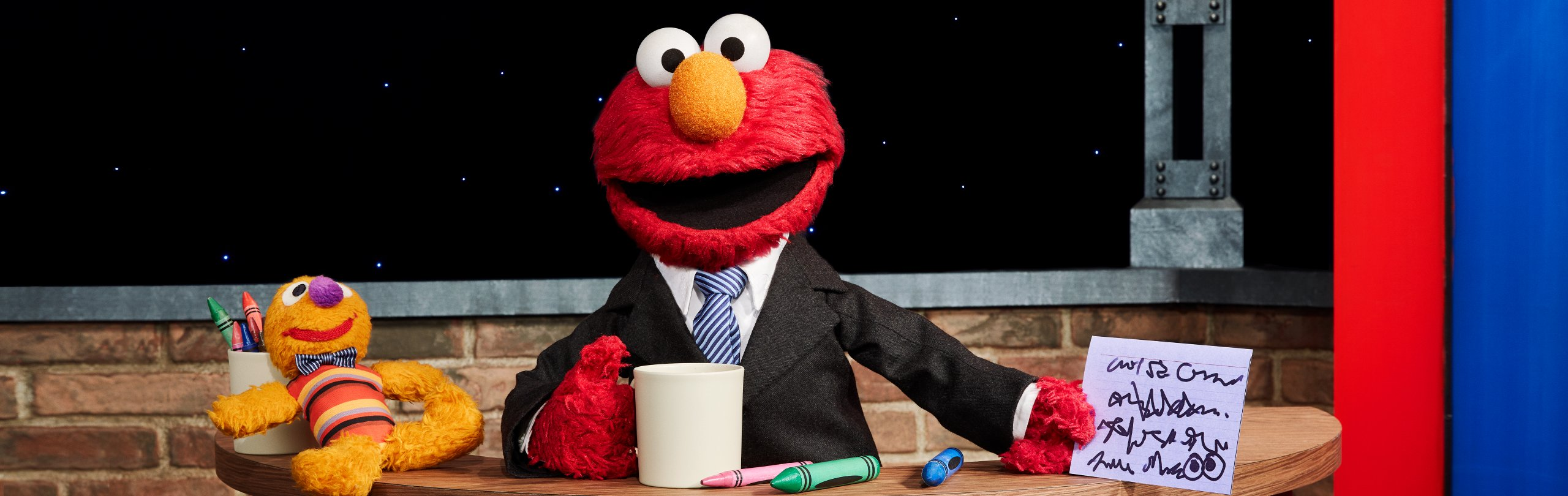 Elmo is wearing a suit and sitting at a desk with a mug of coffee