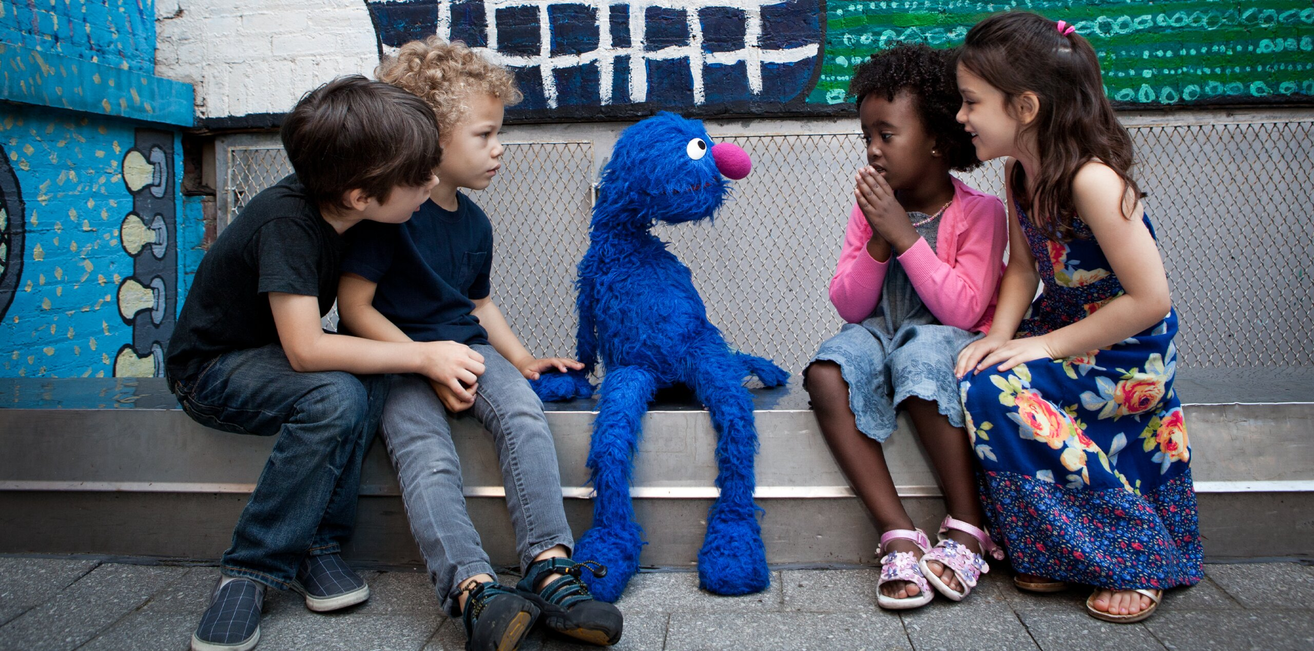 Grover sits on a step with a group of four children looking at him
