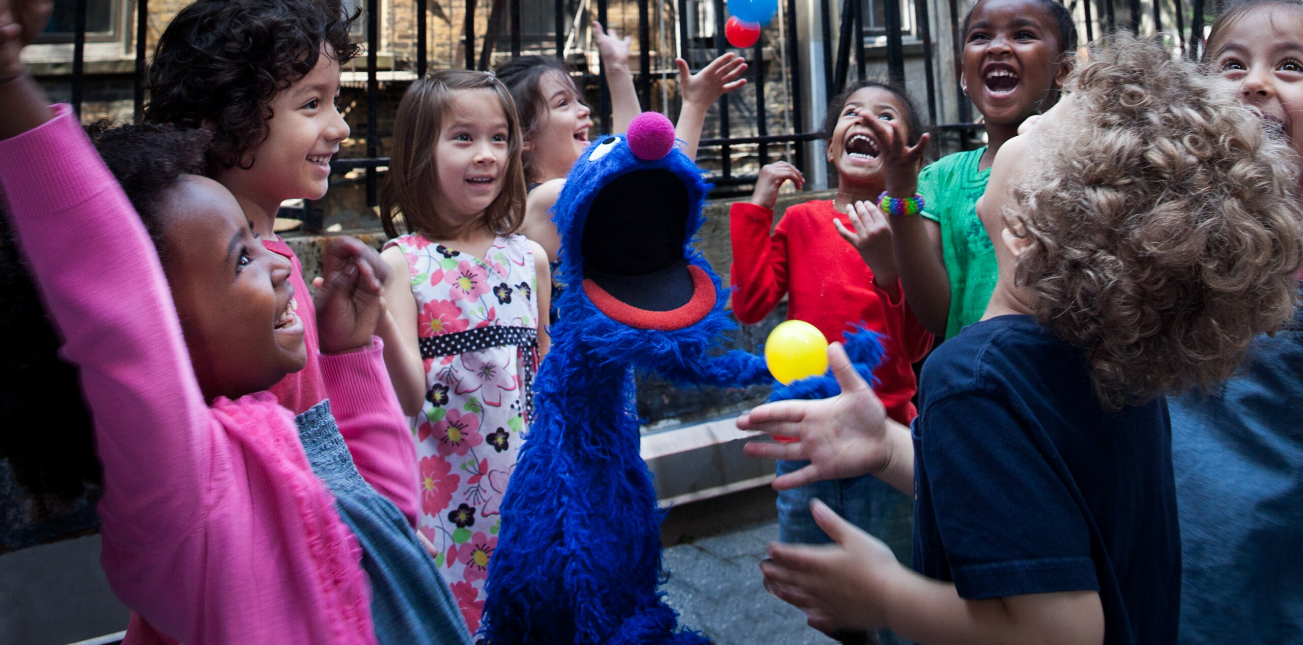 Grover laughs with a group of children outside