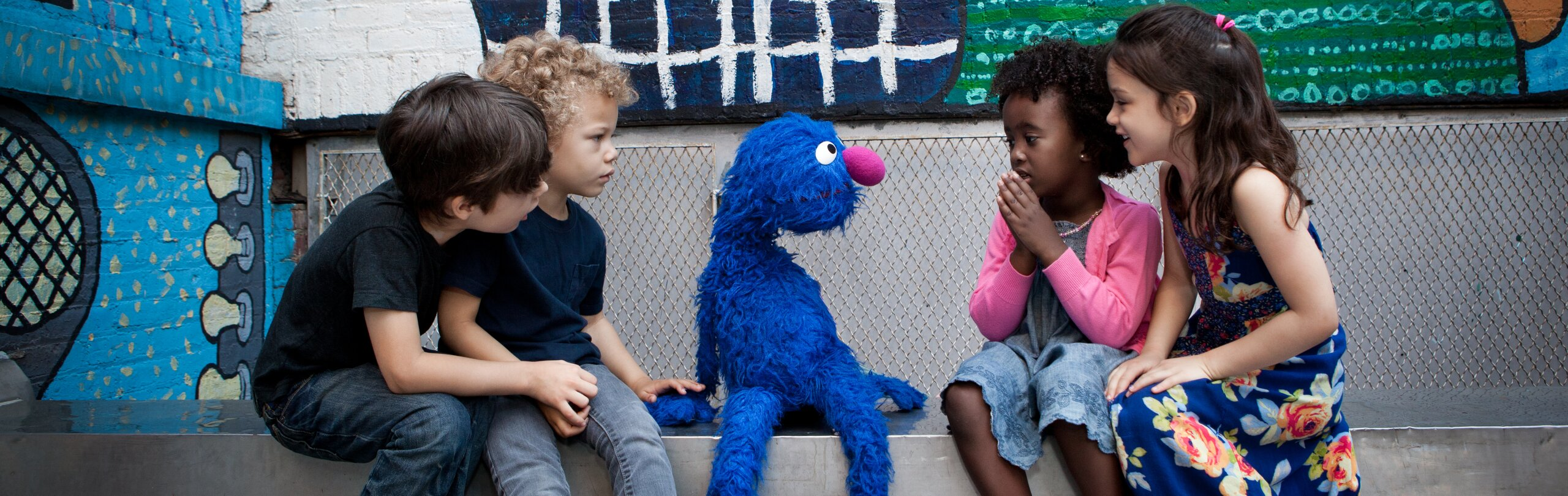 Grover sits on a stoop with a group of four children looking at him