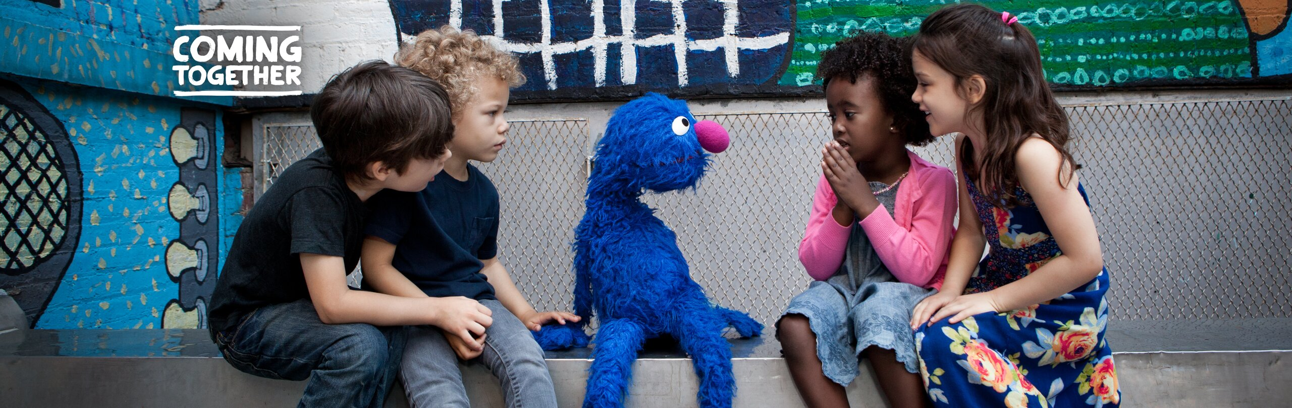 A group of kids sits with Grover on a step outdoors | a logo reading COMING TOGETHER is in the upper left corner